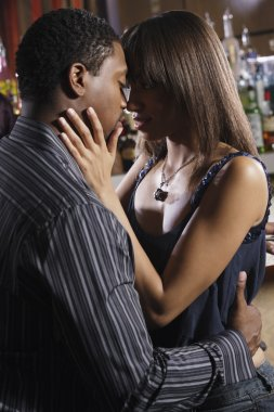 African couple hugging at bar