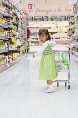 Hispanic girl pushing child's shopping cart