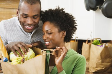 African American couple looking in grocery bag