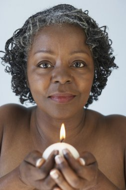 Senior African woman holding candle