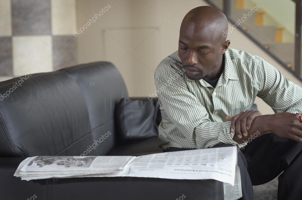 African man reading newspaper on sofa