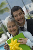 Hispanic man giving gift to mother