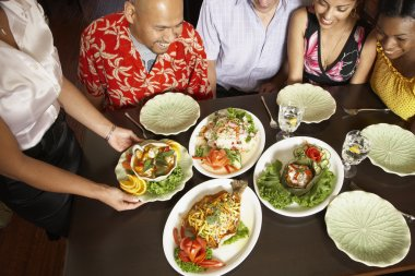Multi-ethnic friends looking at table full of food