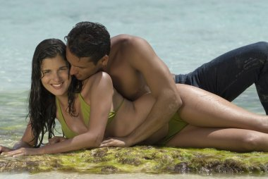 Hispanic couple laying on rock in water