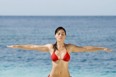 Hispanic woman practicing yoga at beach