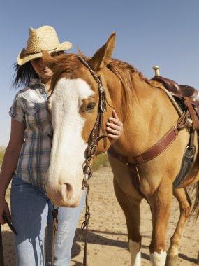 Hispanic woman standing next to horse