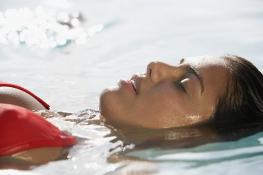 South American woman floating in water