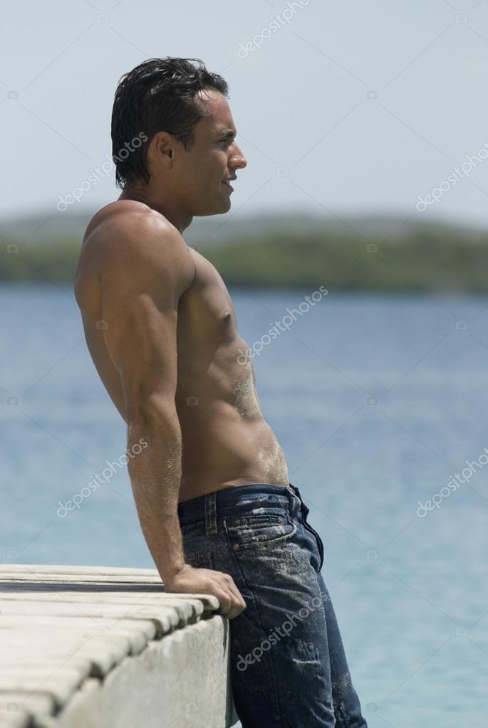 Hispanic man leaning on dock