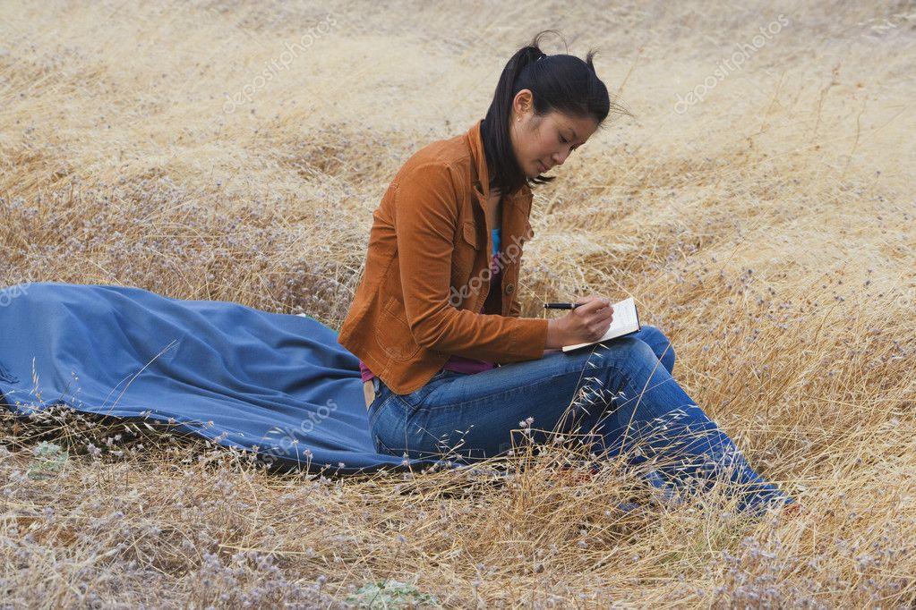 Asian woman writing in journal
