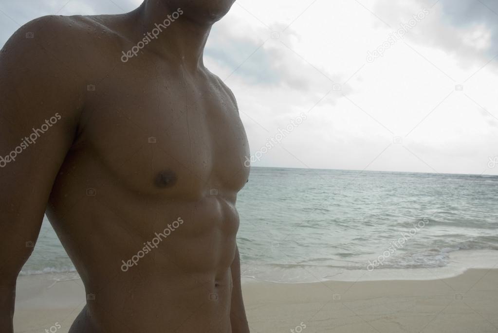 Bare-chested Hispanic man at beach