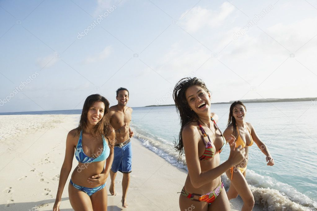 South American friends running at beach