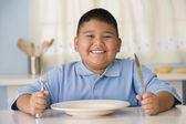 Photo Hispanic boy holding silverware at table