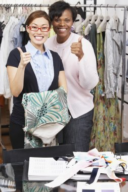 Multi-ethnic fashion designers giving thumbs up