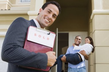 Hispanic real estate agent and African couple in front of house