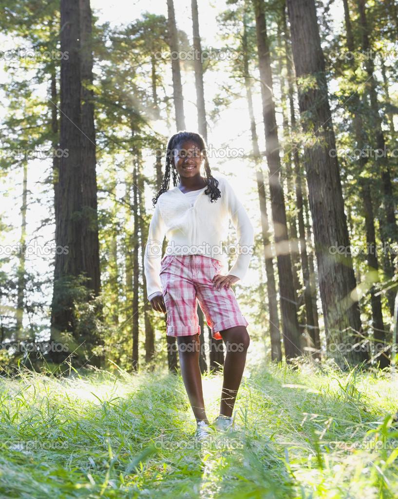 African girl standing in woods