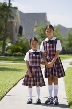 Asian sisters in school uniforms holding hands