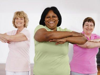 Multi-ethnic women taking exercise class