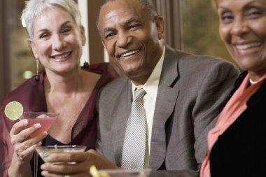 Three senior friends drinking cocktails