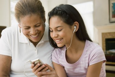 Hispanic grandmother and granddaughter listening to music on mp3 player