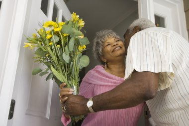 Senior African man giving flowers to wife in doorway