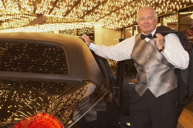Senior man in tuxedo next to limousine