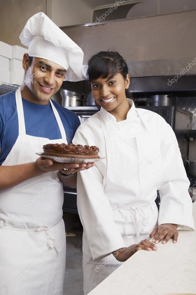 Multi-ethnic pastry chefs with cake