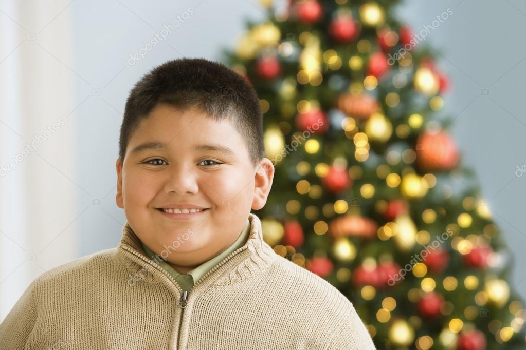 Hispanic boy smiling near Christmas tree