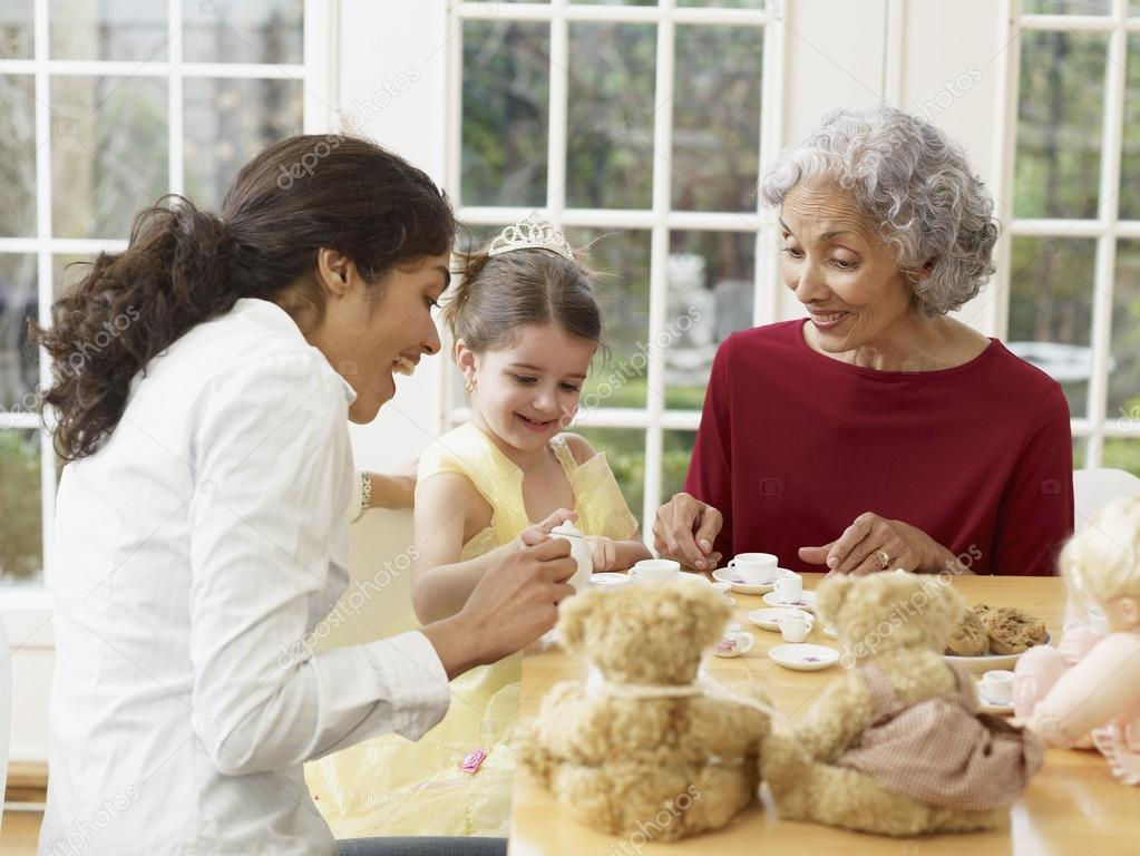Multi-generational Hispanic family having tea party