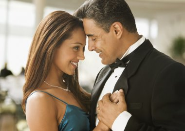 Hispanic couple dancing in eveningwear