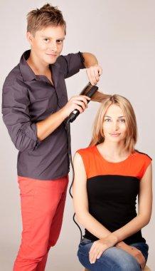 Stylist ironing hair