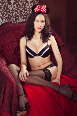 Brunette pin up model posing dressed in underwear and bow of  Mi