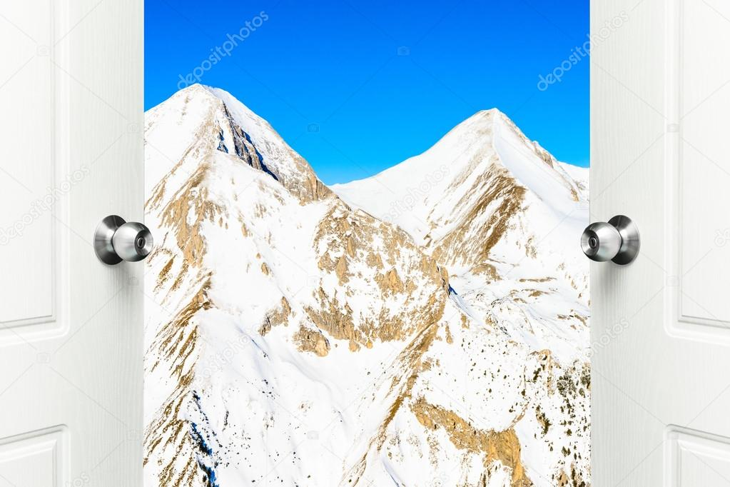 white door open with views of the peaks of snowy mountains