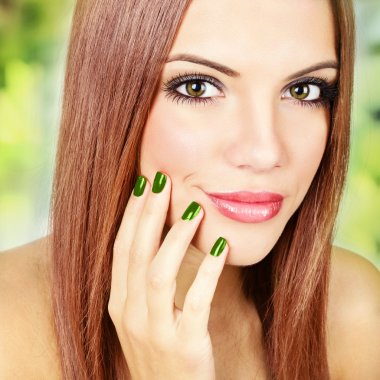 Gorgeous redhead with metallic green manicure