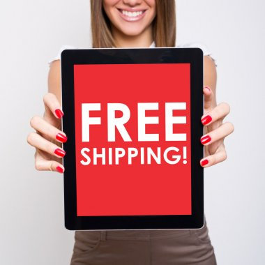 Smiling young woman holding tablet that states free shipping