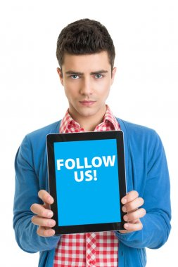 Modern young man holding tablet pc that states follow us