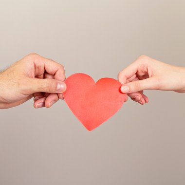 Man and woman hands holding red paper heart