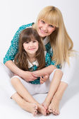 Fotografie Mother and daughter with long hair with bangs hugging and smiling