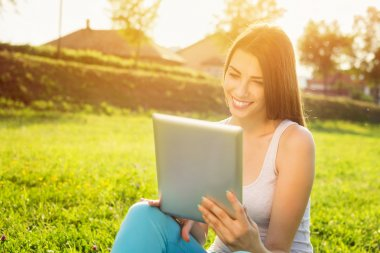 Happy young woman with tablet in park on sunny summer day