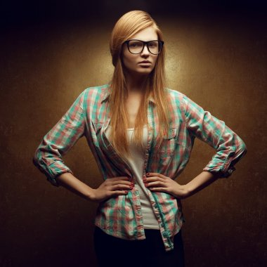 Portrait of a young beautiful red-haired wearing trendy glasses