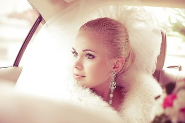 Portrait of a beautiful blonde bride sitting in the wedding car
