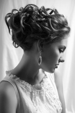 Emotive arty portrait of a fashionable queen-like young woman in