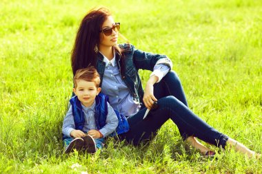 Portrait of fashionable baby boy and his stylish mother in trend