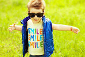 Stylish baby boy with ginger (red) hair in trendy sunglasses and