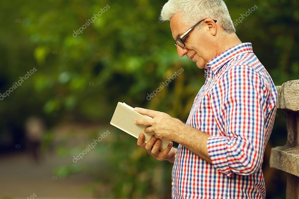 c54b4550a07c Successful man concept. Profile portrait of a smiling happy mature (old) man  in trendy casual shirt   glasses reading book in the park. Sunny summer day.