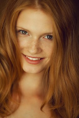 Portrait of a smiling beautiful red-haired (ginger) girl with fu