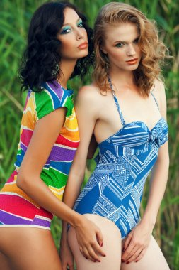 Portrait of two gorgeous young women (girlfriends) in trendy col