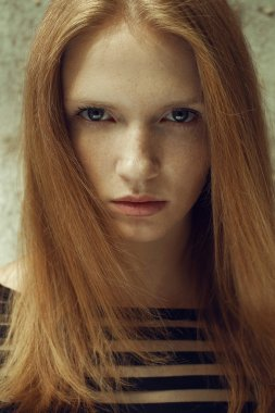 Portrait of a beautiful red-haired (ginger) model with freckles