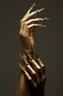 Art Manicure Concept. Beautiful golden hands with golden long ar