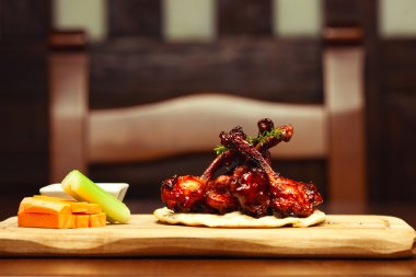 American food concept. Chicken wings with celery, carrot and sau