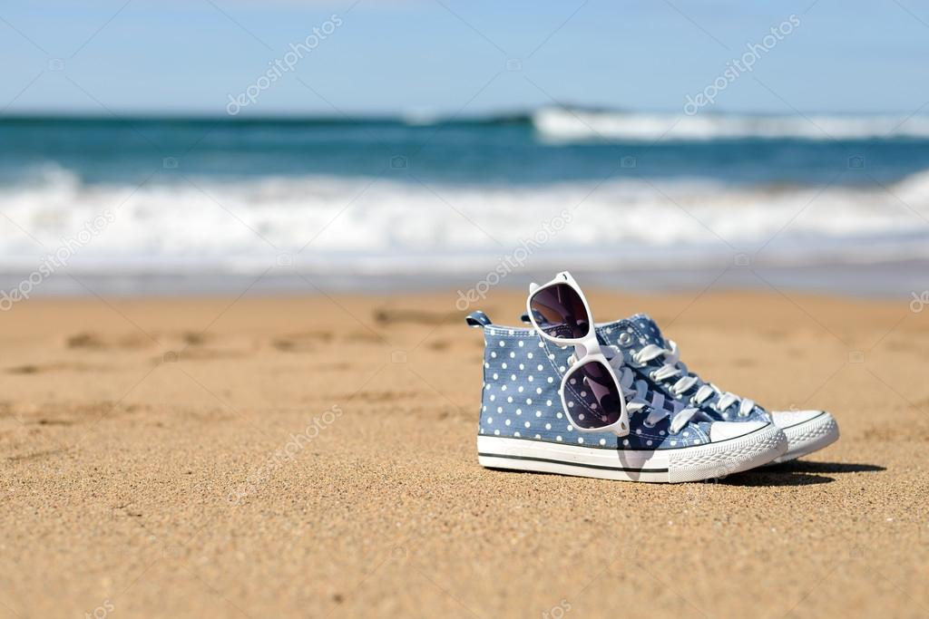 80509fb21ad2 Summer vacation and relaxing concept. Female casual sneakers and sunglasses  on beach. — Photo by Dirima